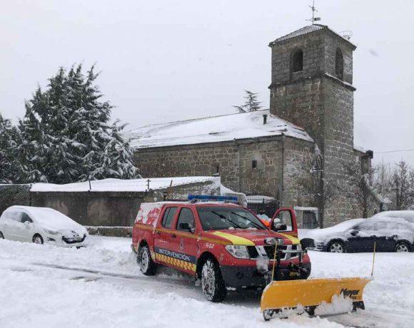 Un vehículo de Protección civil durante la nevada de Filomena con la iglesia de Moralzarzal al fondo