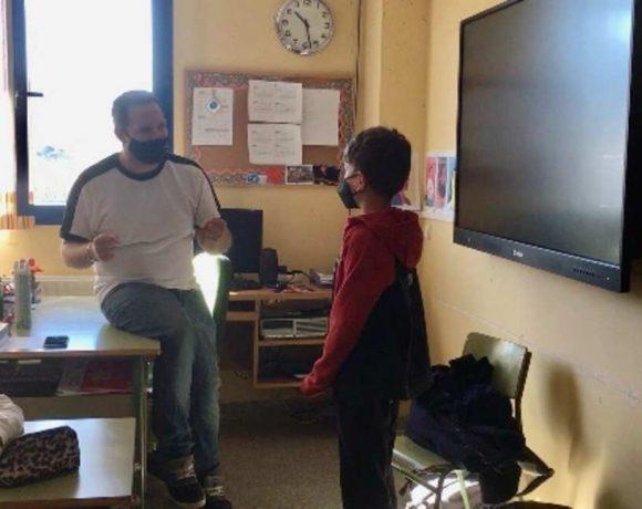 Unos niños atienden en el aula las instrucciones de un adulto