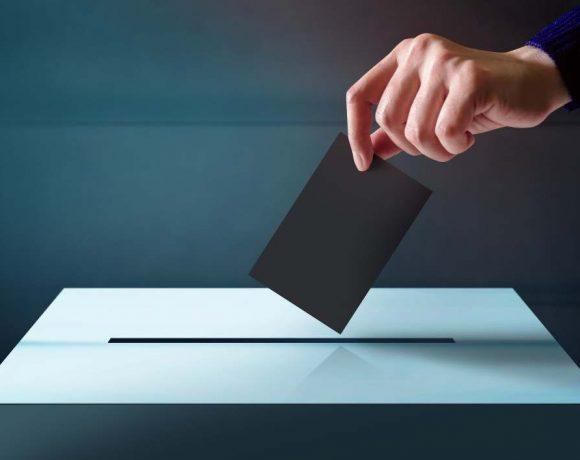 Una mano introduce un voto en una urna