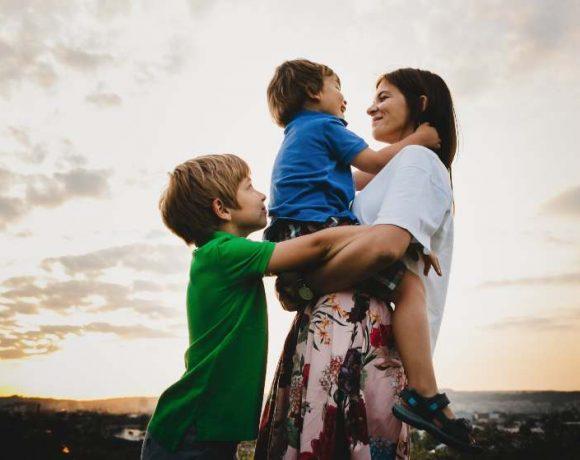 Una madre con dos niños, uno de ellos en sus brazos