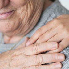 Una mano de persona sobre el hombro de una anciana