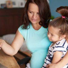 Una adre explica algo a su hija con un portátil