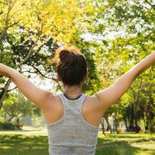 Una mujer de espaldas con los brazos extendidos hacia los árboles
