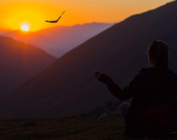 Una mujer contempla el atardecer en una montaña