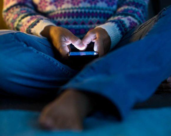 Una persona mira el móvil en la oscuridad