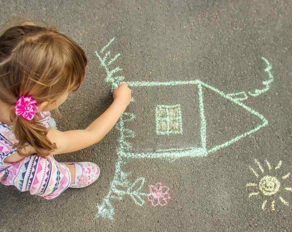 Una niña dibuja en el suelo una casa con una tiza